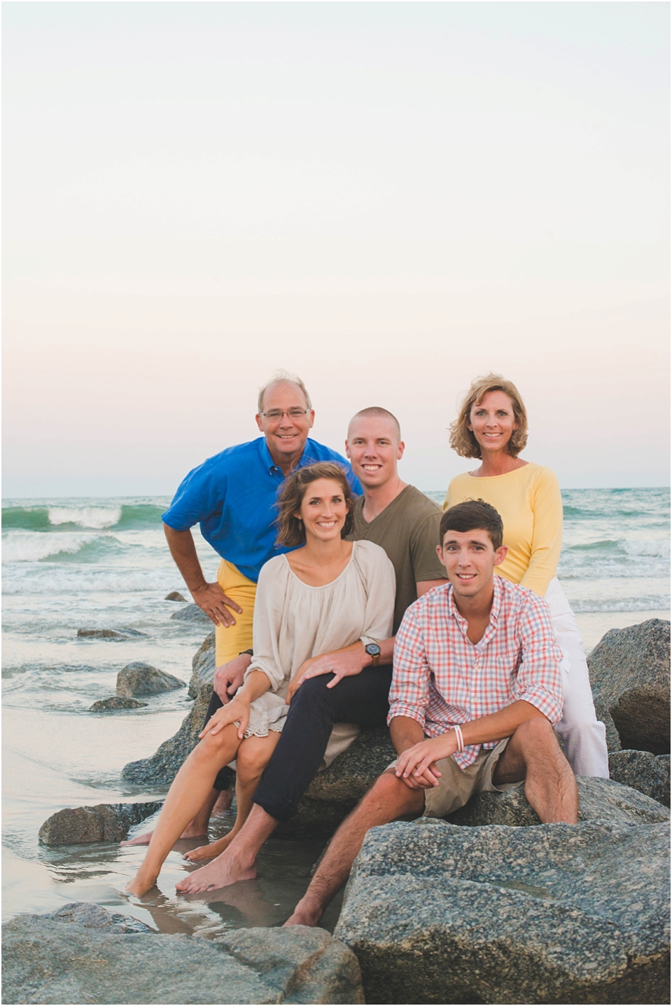 family sitting on the rocks at the beach for pictures