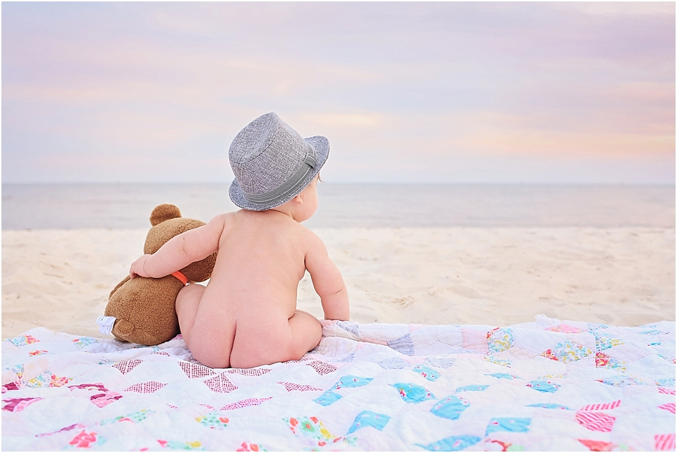little baby on the sand at the beach for pictures