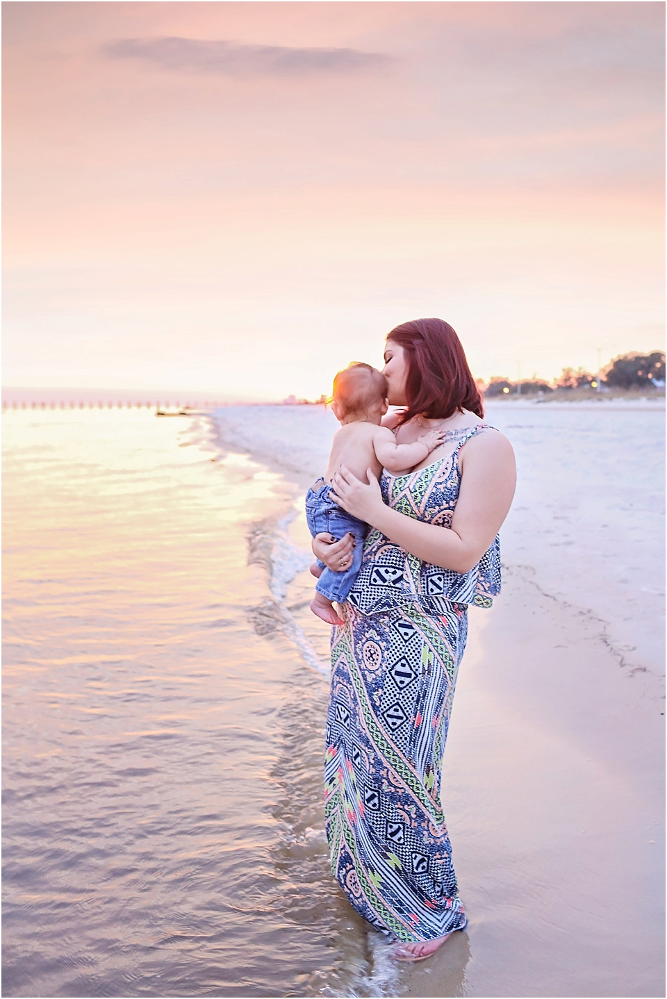 sunset picture of a mom and baby posing for pictures