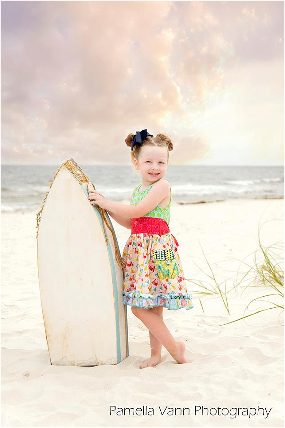 little girl posing with a boat at sunset for beach portraits