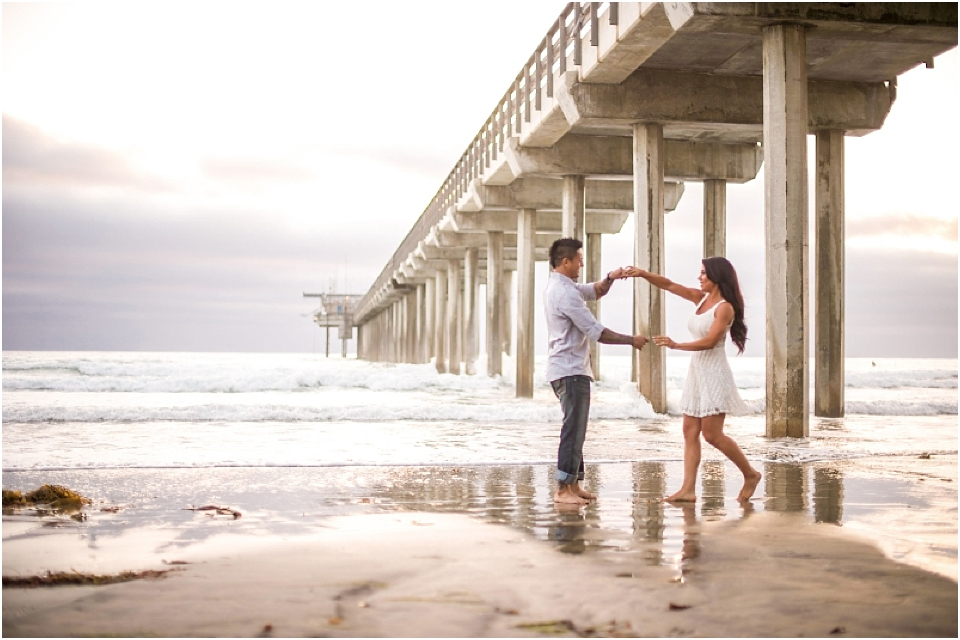 engaged couple dancing on the beach for pictures