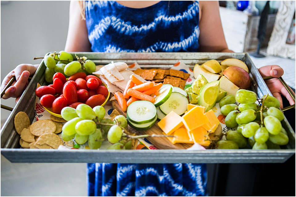 a tray of travel snacks with grapes, cucumbers, carrots, tomatoes, cheese, crackers