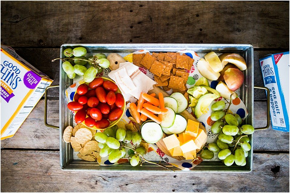 a tray of vacation snacks for a long road trip, grapes, crackers, GOOD THINS, tomatoes
