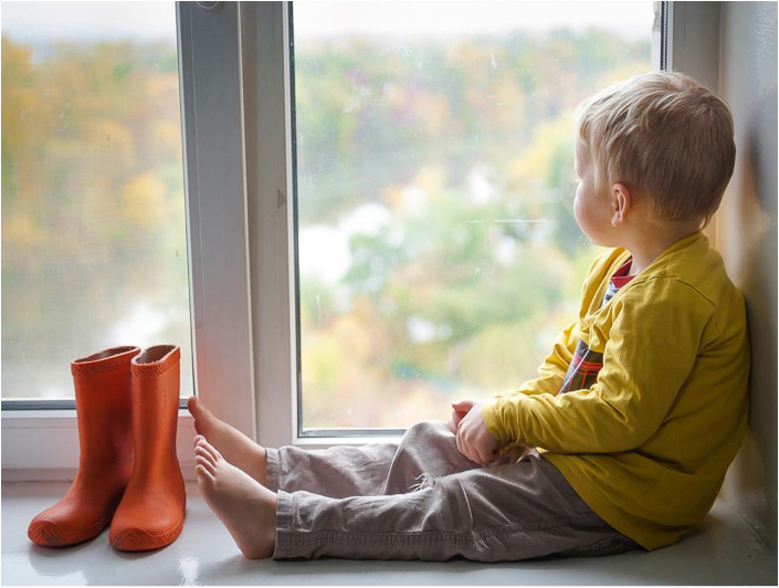 toddler boy sitting inside on a rainy day looking out of a window