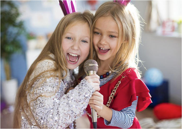 two kids singing into a microphone enjoying imaginative play