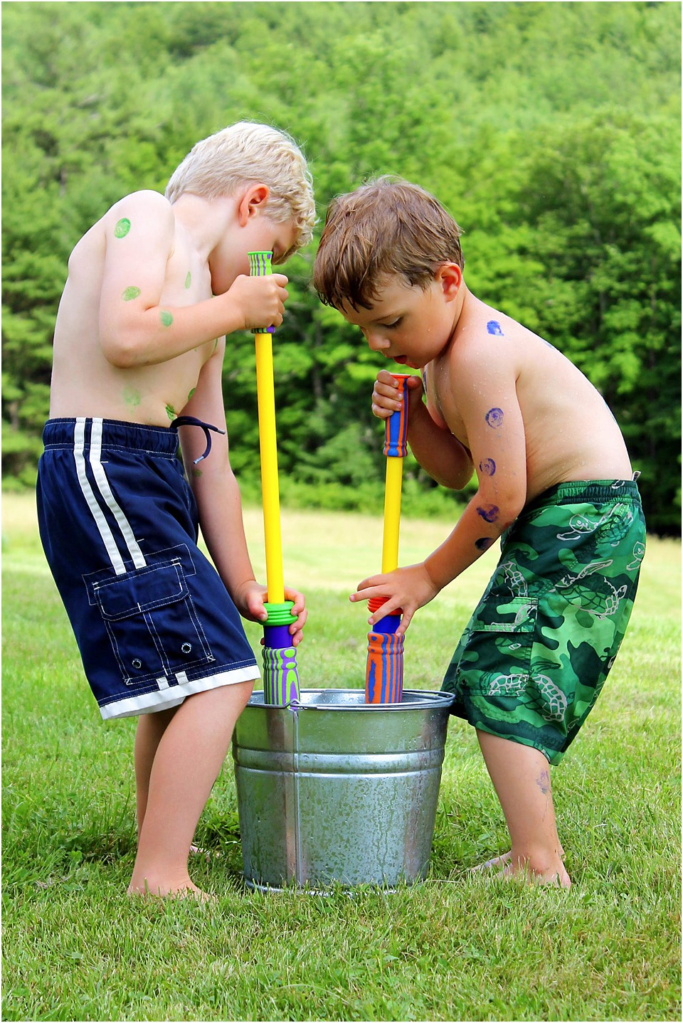 two boys with water guns filling up and having outside fun