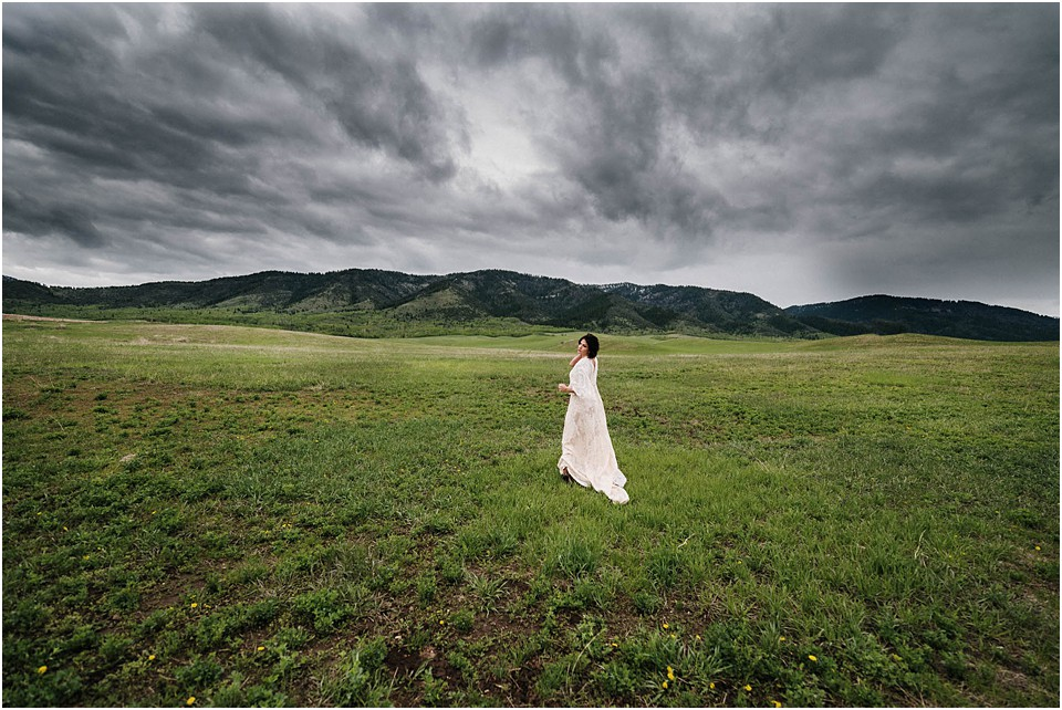 lady in a field with clouds rolling in over mountains