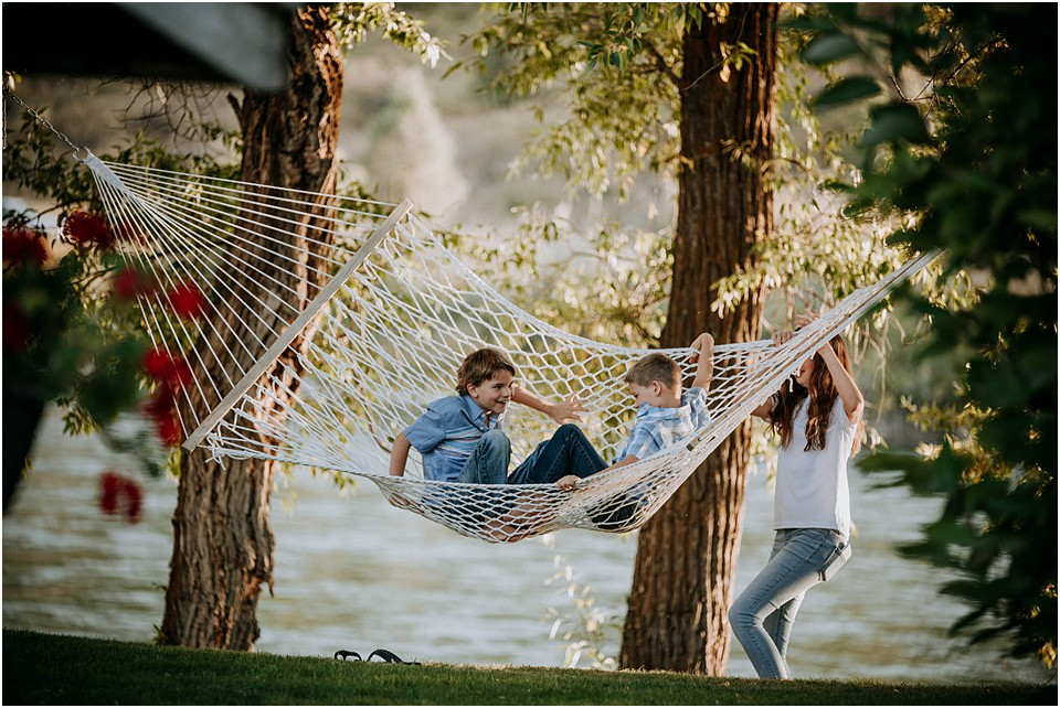 family swinging in a hammock with teen girl pushing them