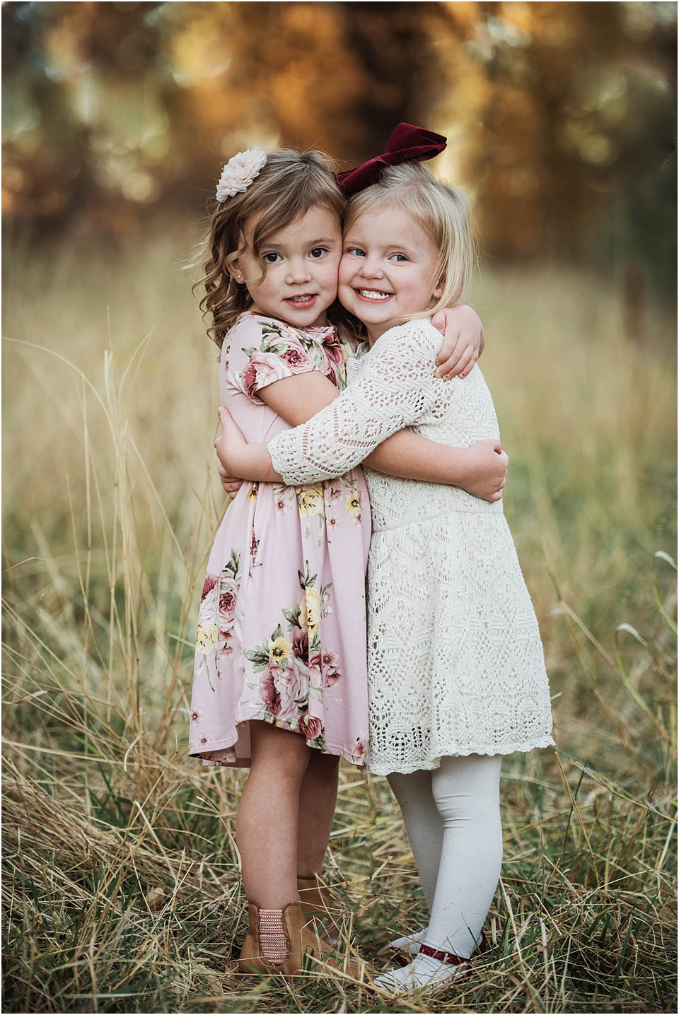 two young girls side hugging smiling for camera