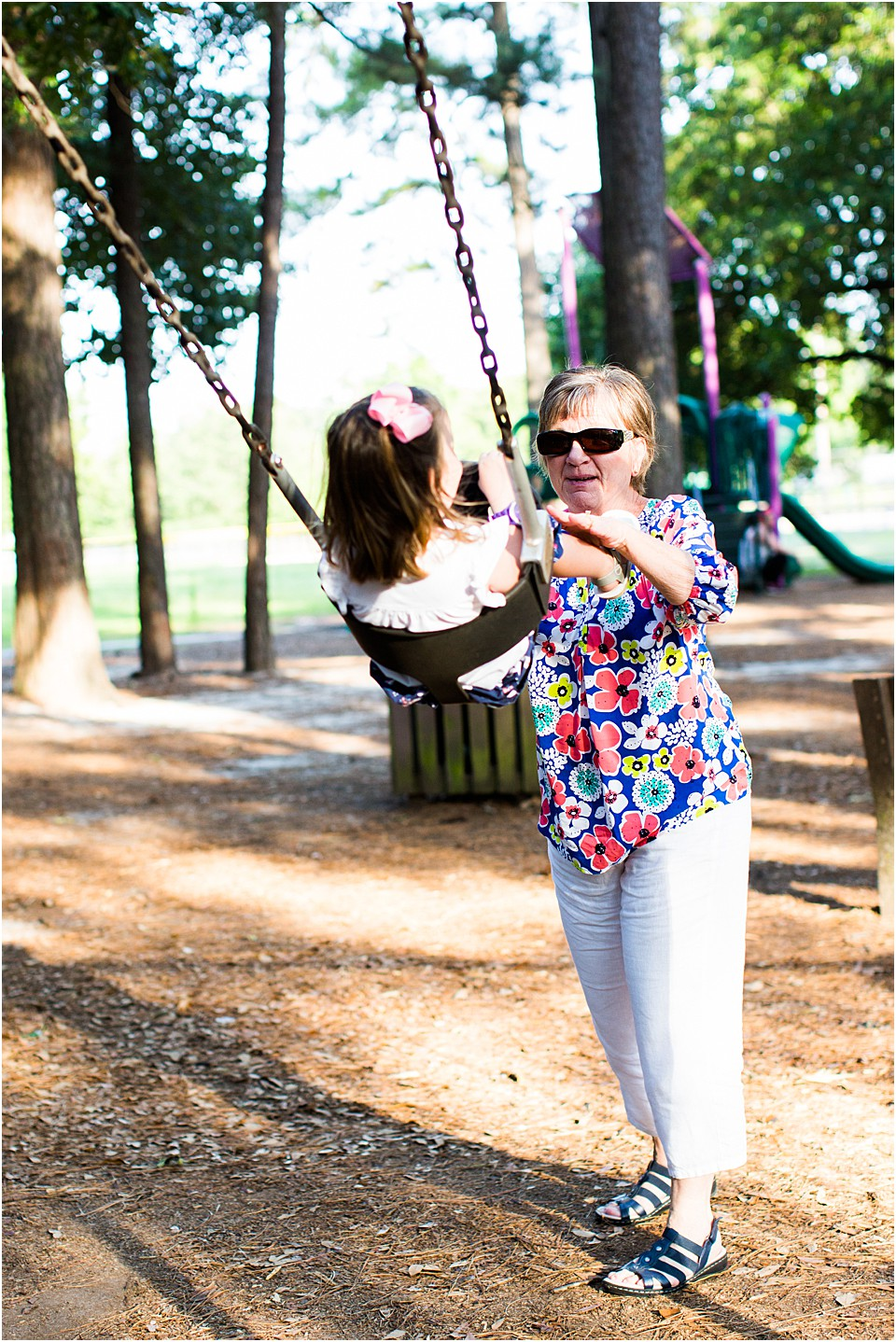 grandmother pushing toddler in a swing