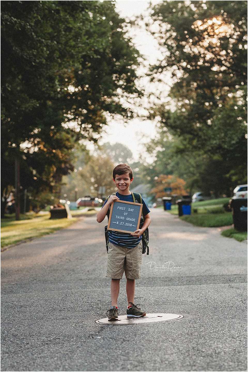 first day of school sign with a letter board held by a young boy