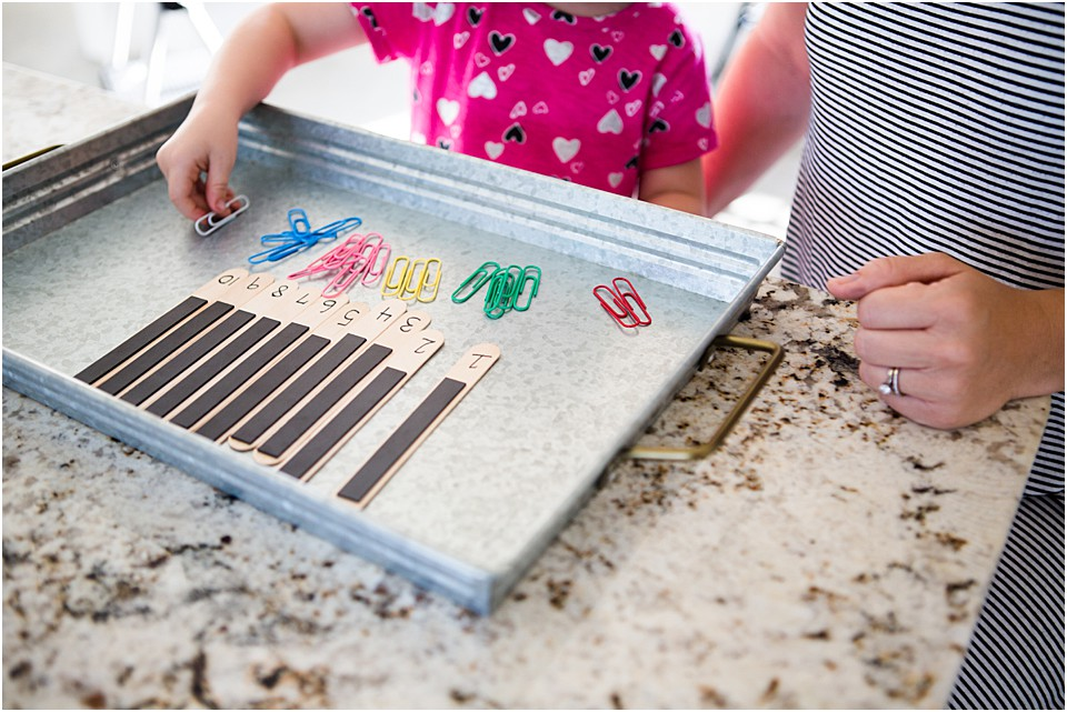 counting paper clips placed onto a magnet on a popsicle stick by a preschooler