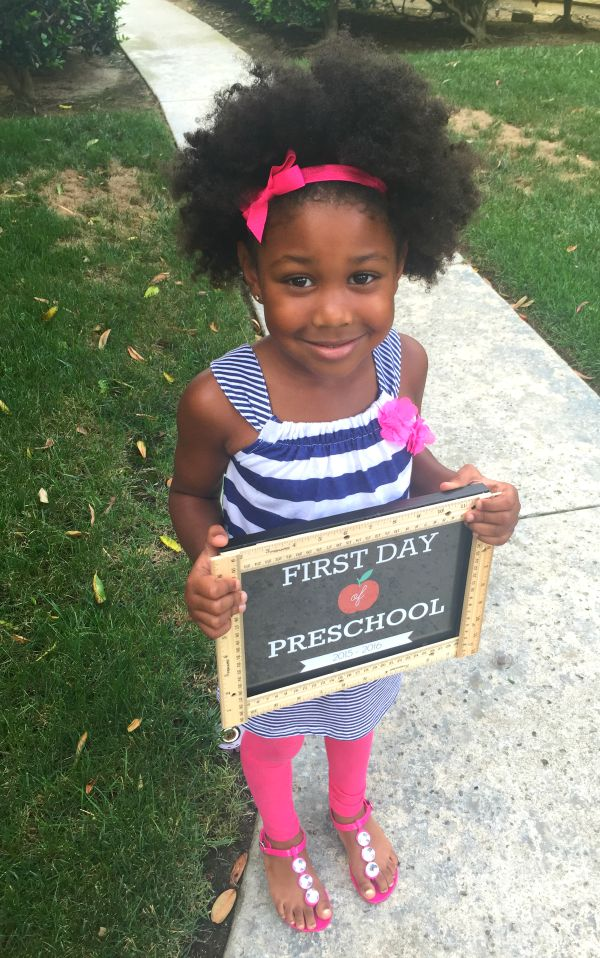 Little Girl holding a First day of School Sign