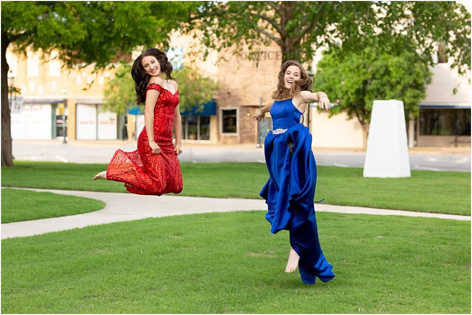 high school senior girls in prom dresses jumping