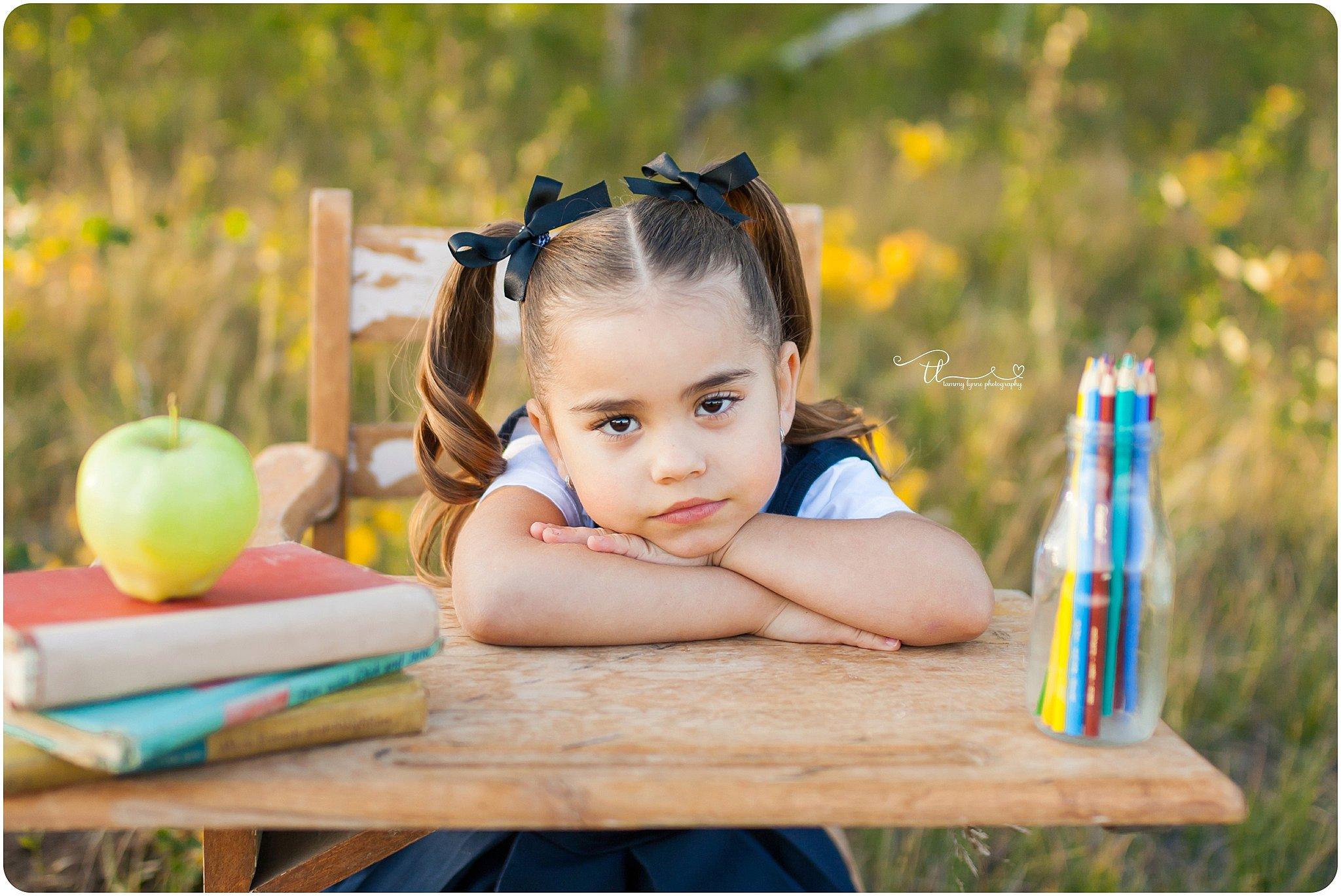 preschooler sitting at vintage desk with photo props
