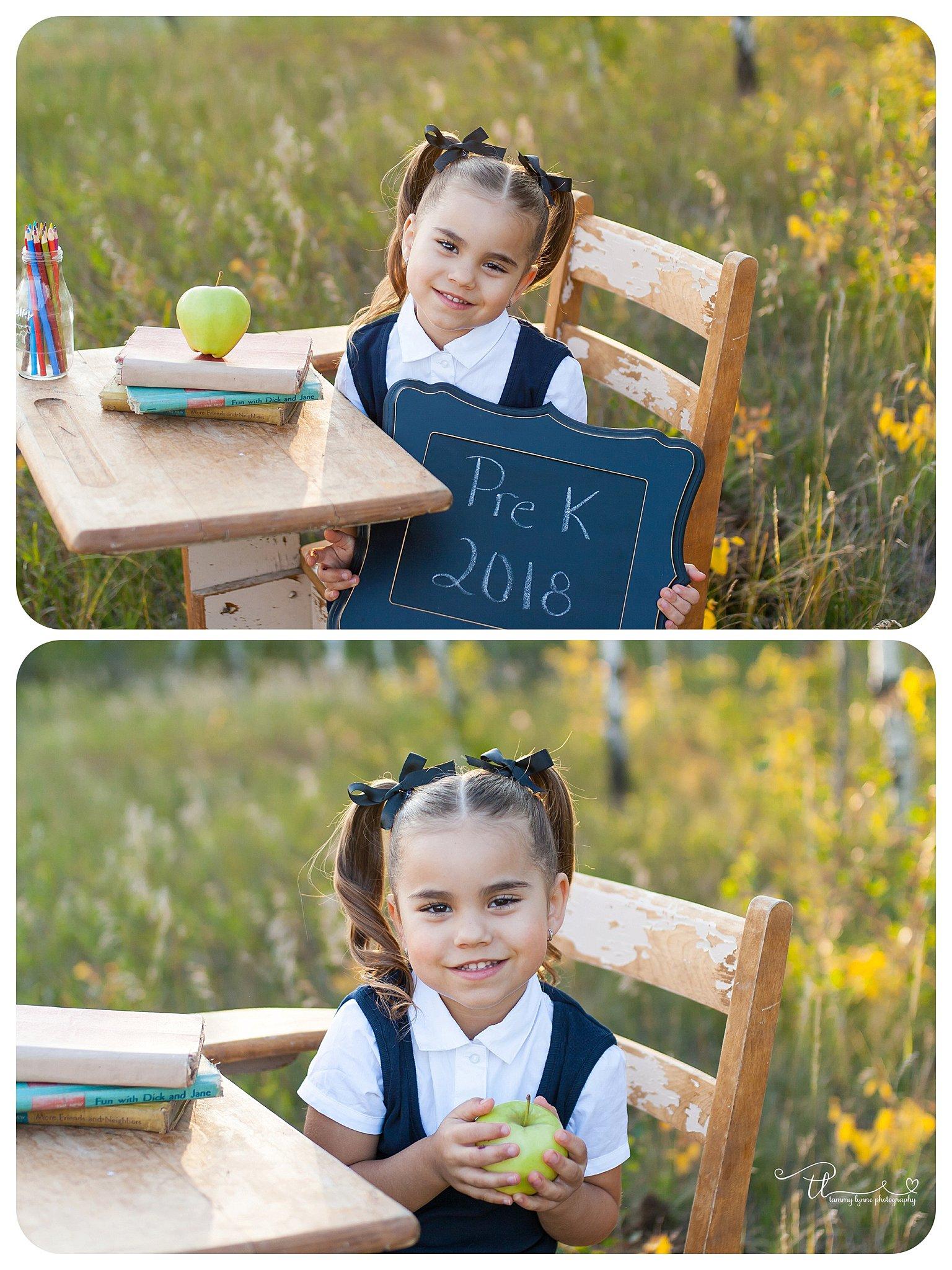 student at vintage school desk holding a grade sign