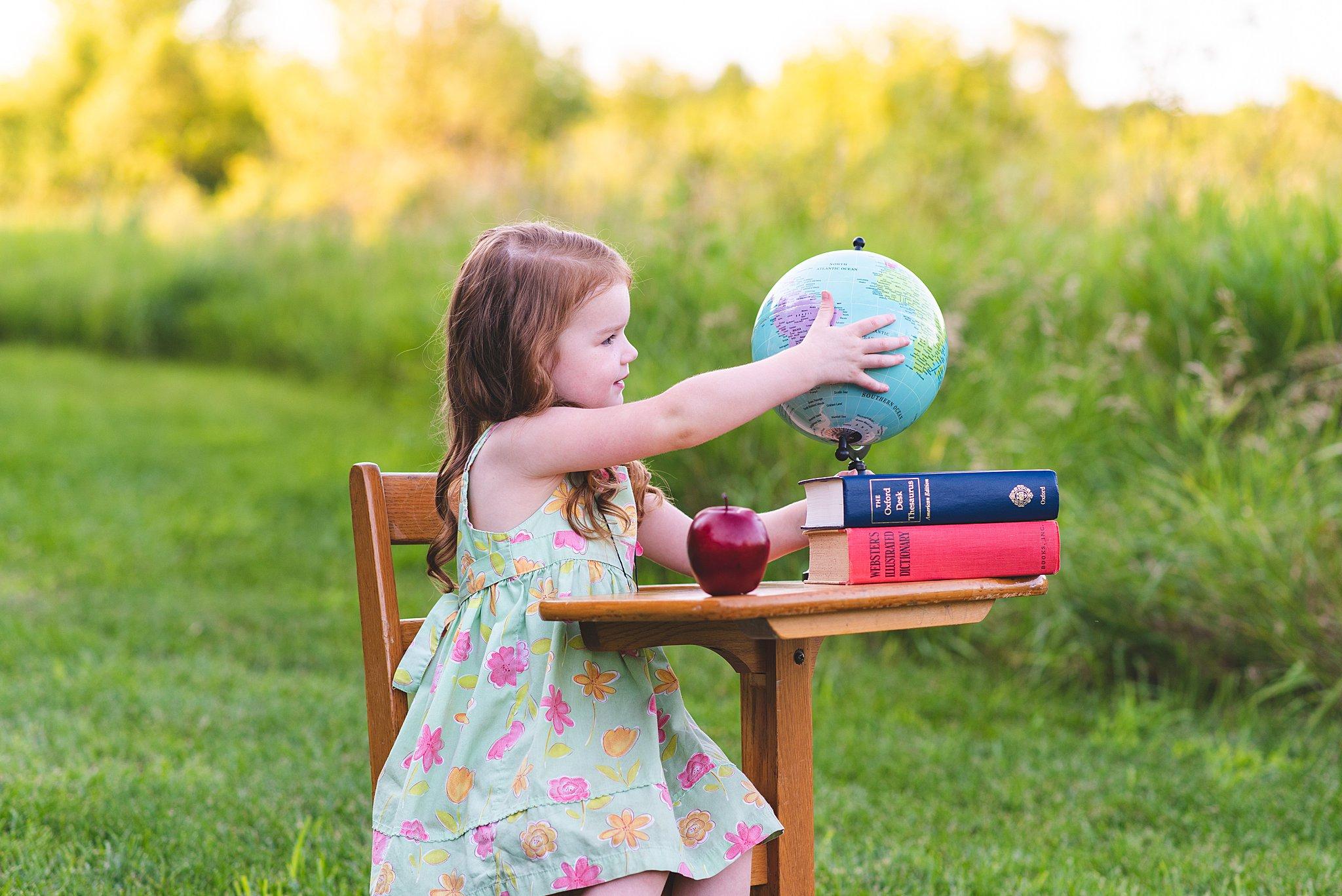 preschooler touching a vintage globe