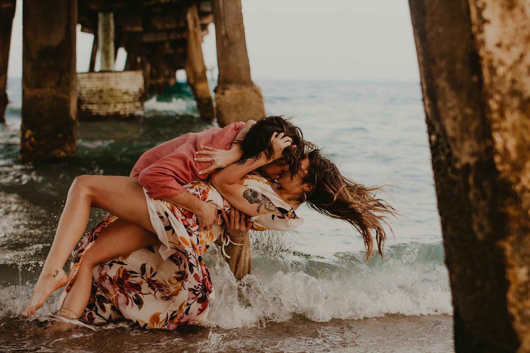 couple at the beach kissing for pictures