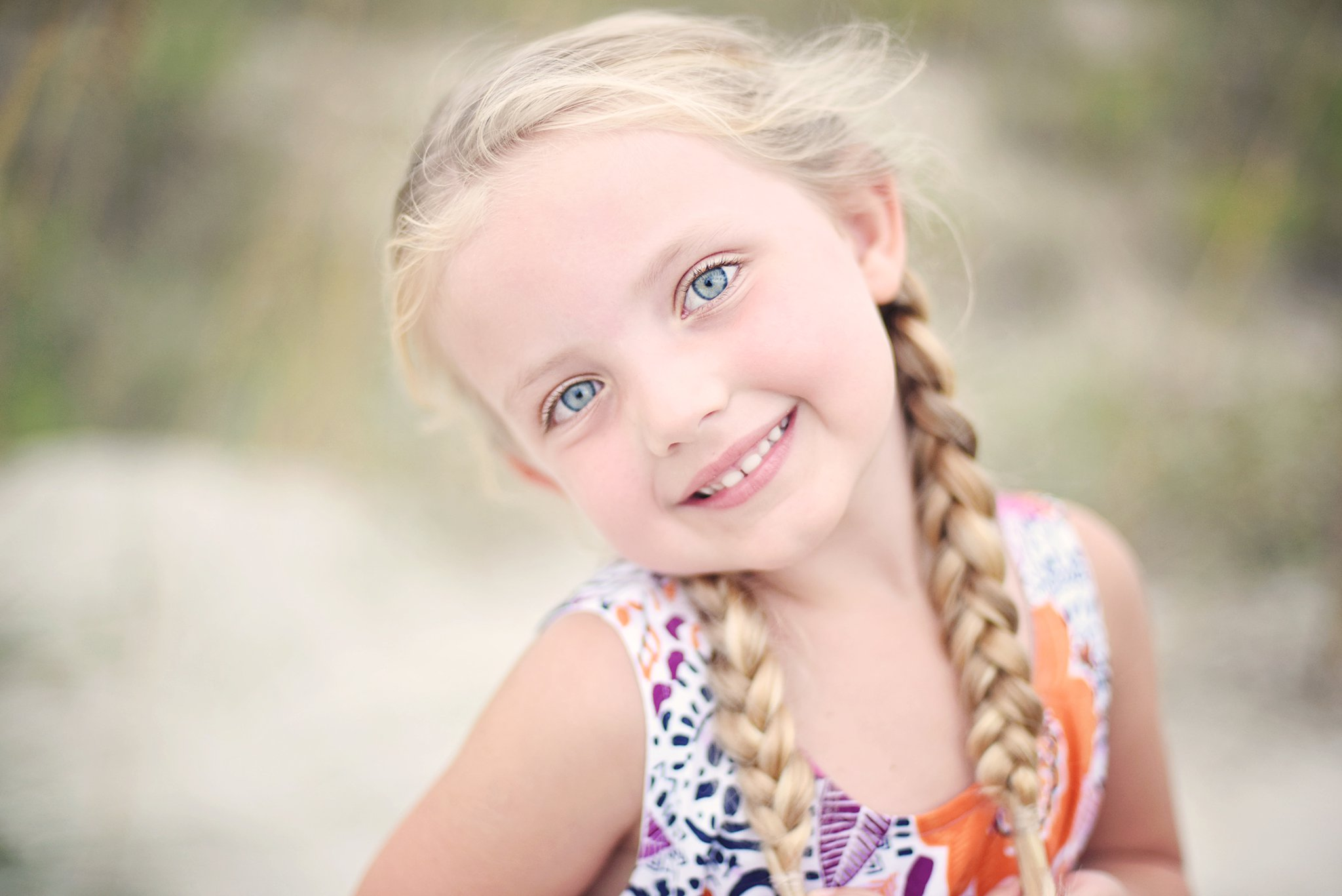 little girl smiling for portraits on the beach