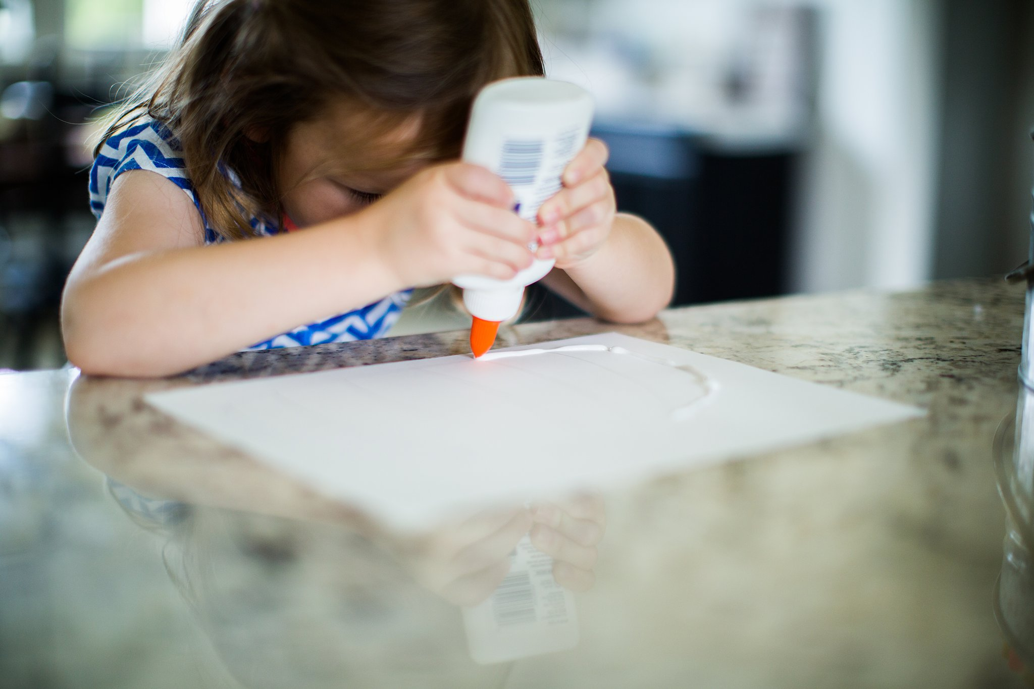 preschooler using glue for salt painting design
