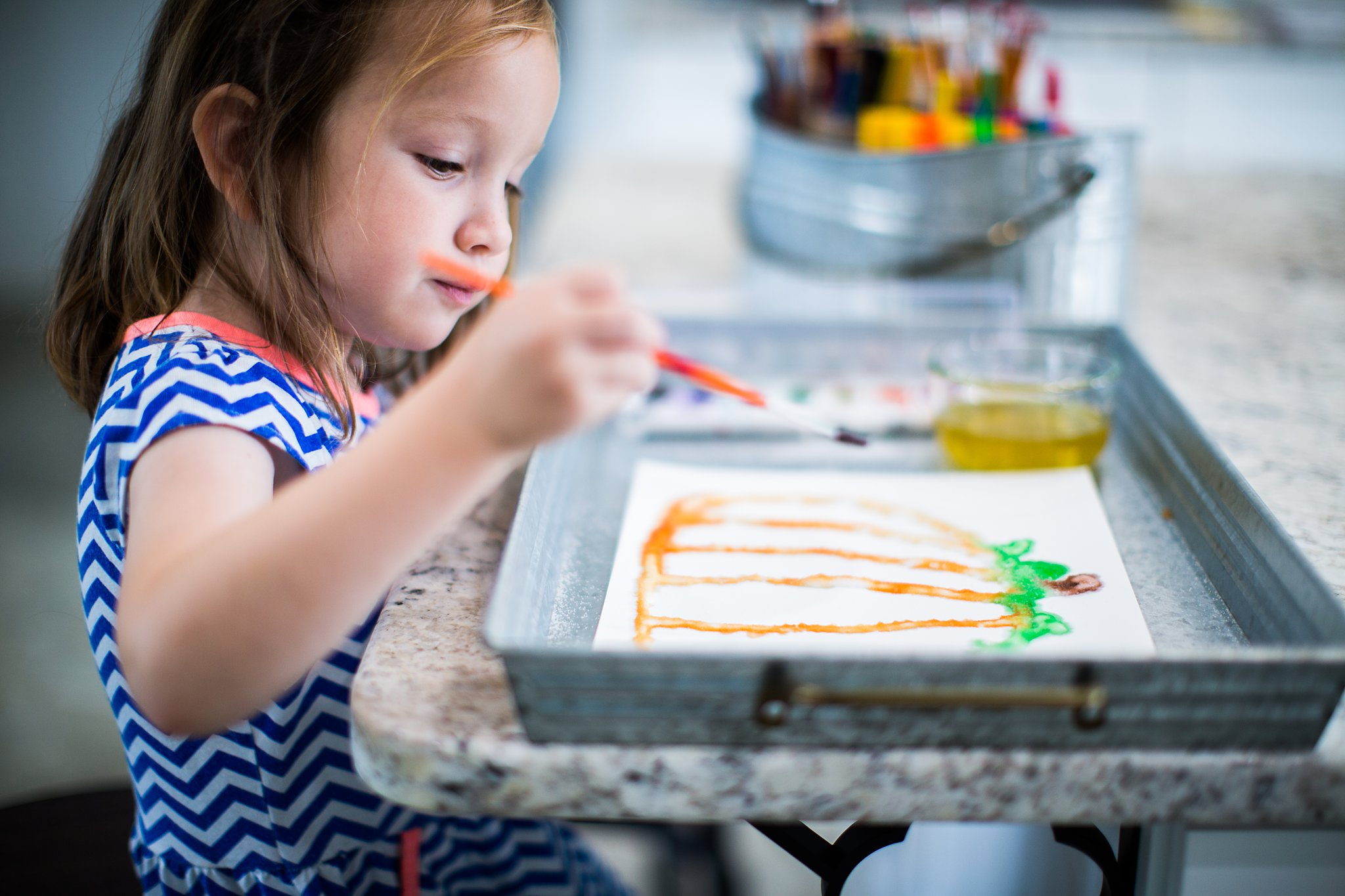 little girl painting a pumpkin with salt art