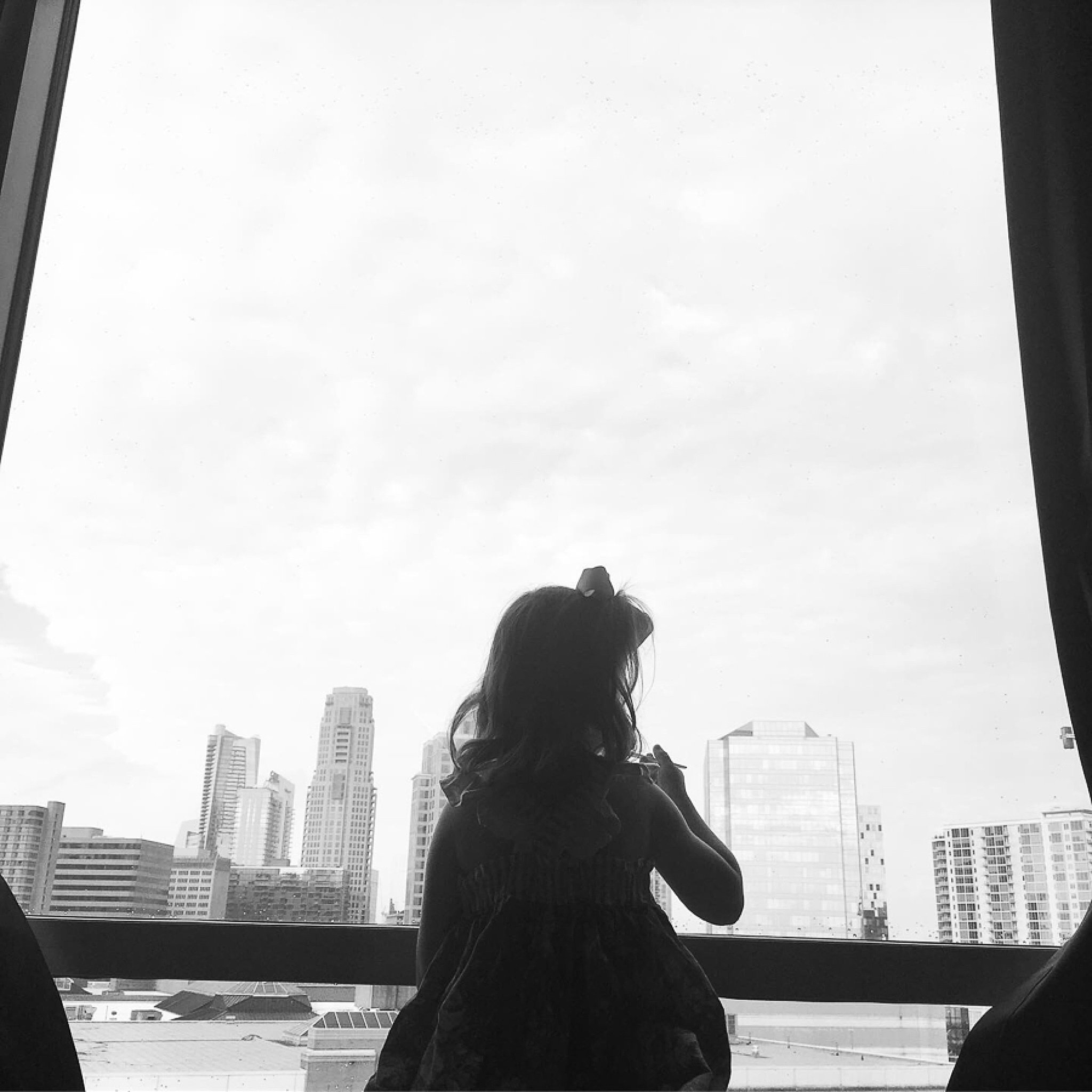 Little girl looking out hotel window at the view of downtown Atlanta