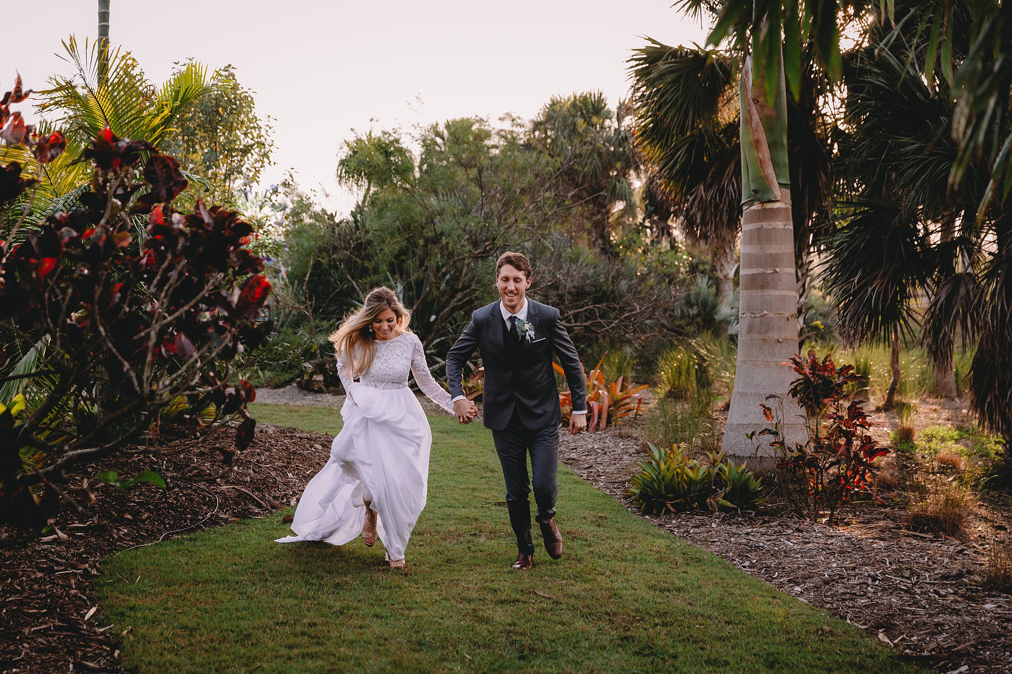 bride and groom running through garden