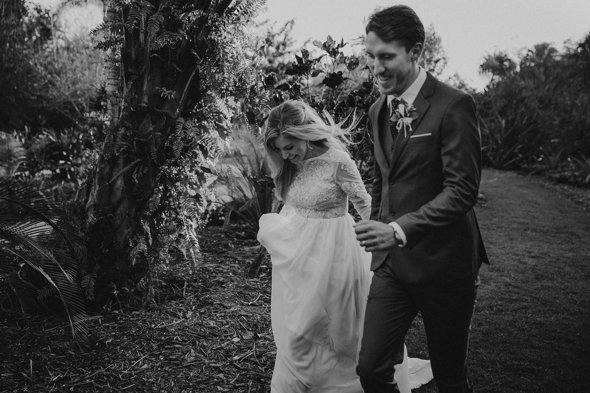 bride and groom laughing while walking in garden
