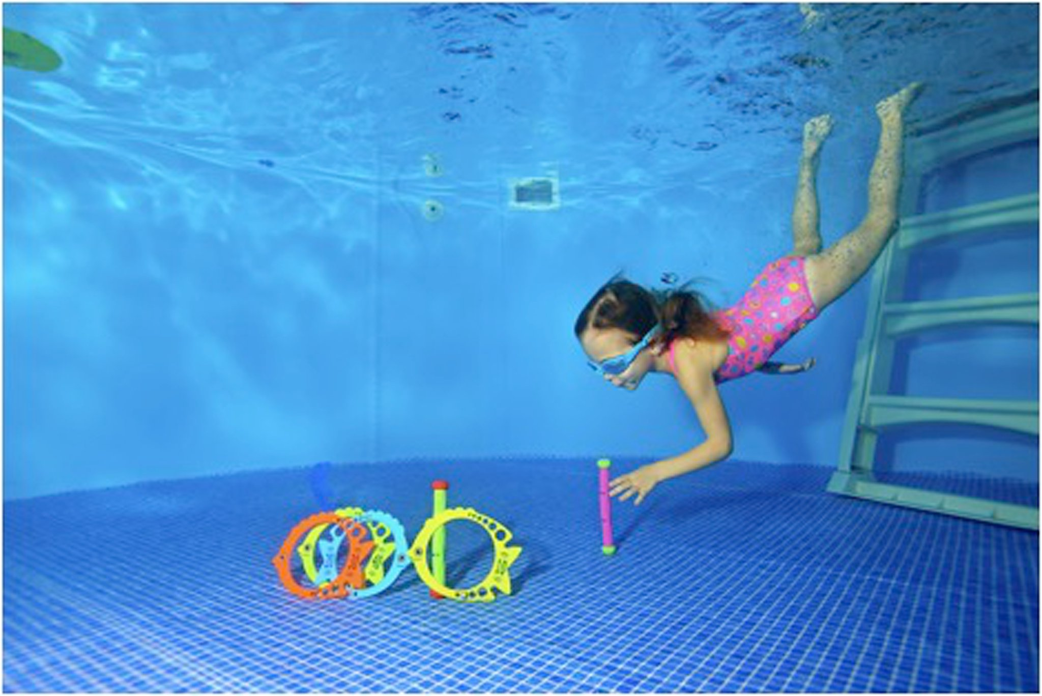 girl diving in a pool picking up rings