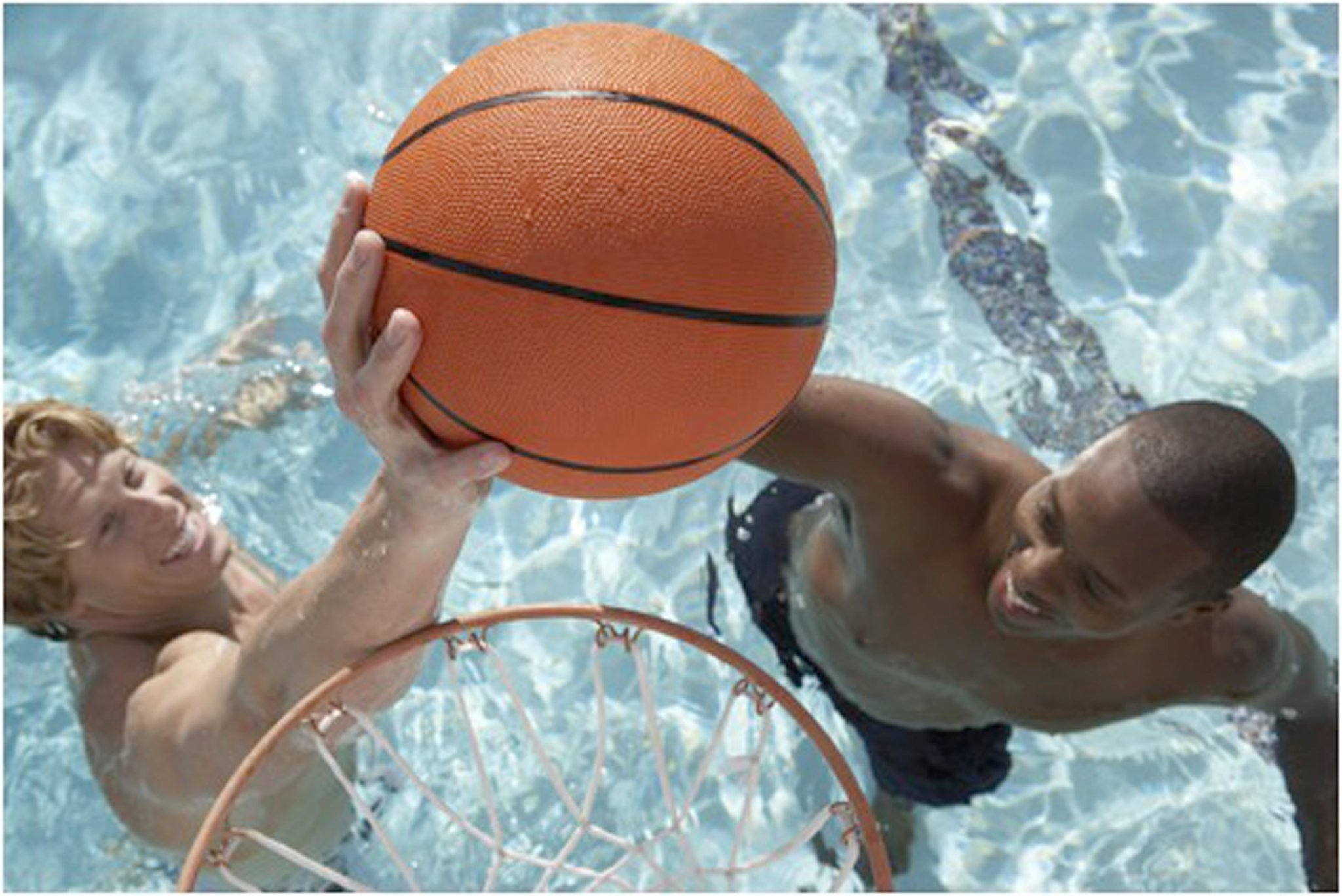 boys playing a basketball game in the pool