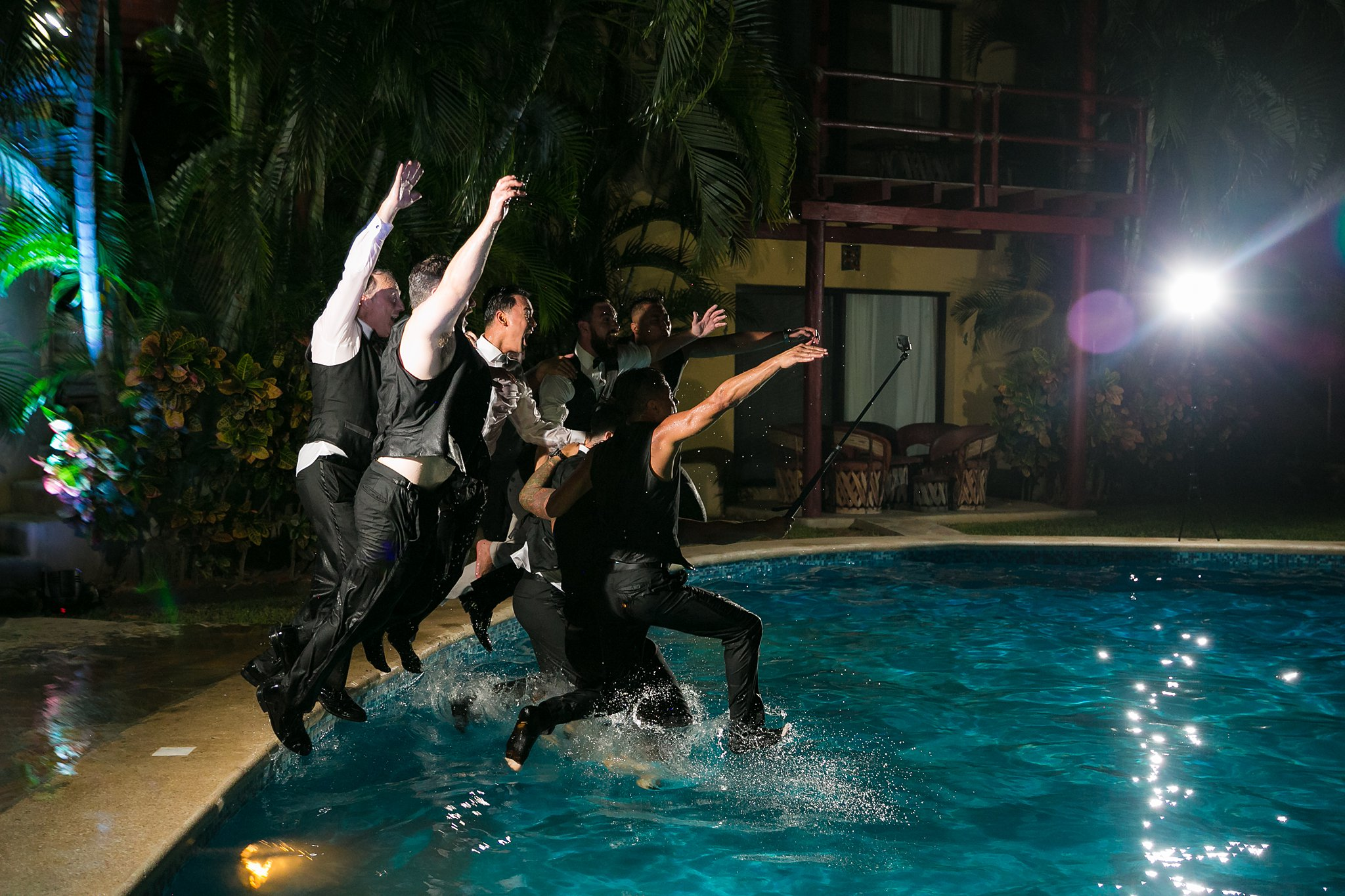 groomsmen jumping into a pool after the wedding