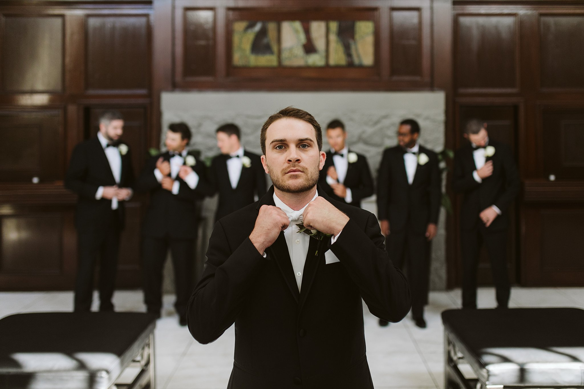 groom adjusting bowtie with groomsmen in the background