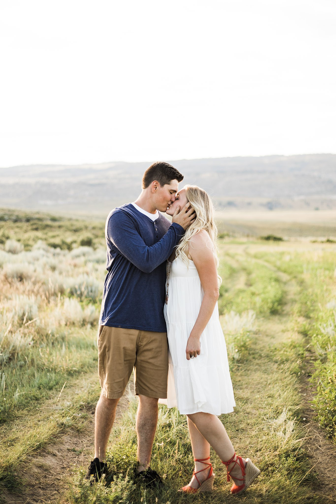 a couple kissing in the prairie for engagement pictures