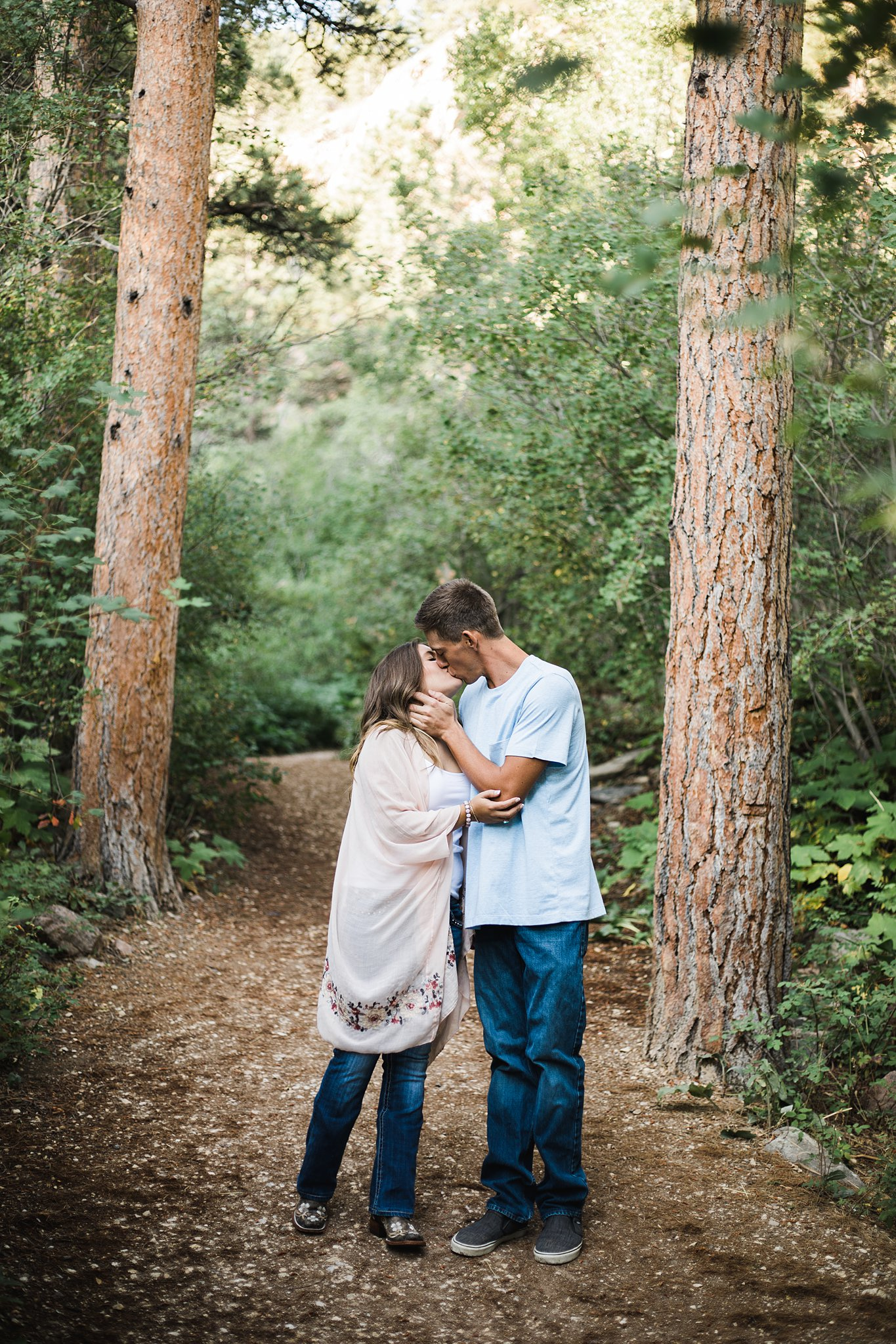 a couple kissing in the forest