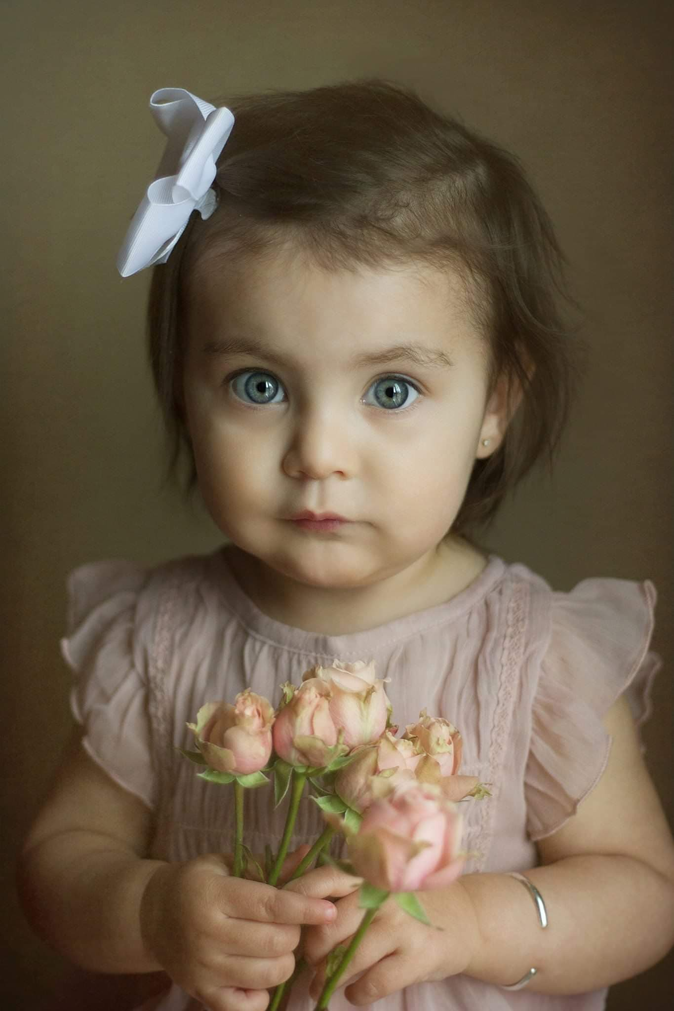 toddler holding flowers posing for studio pictures