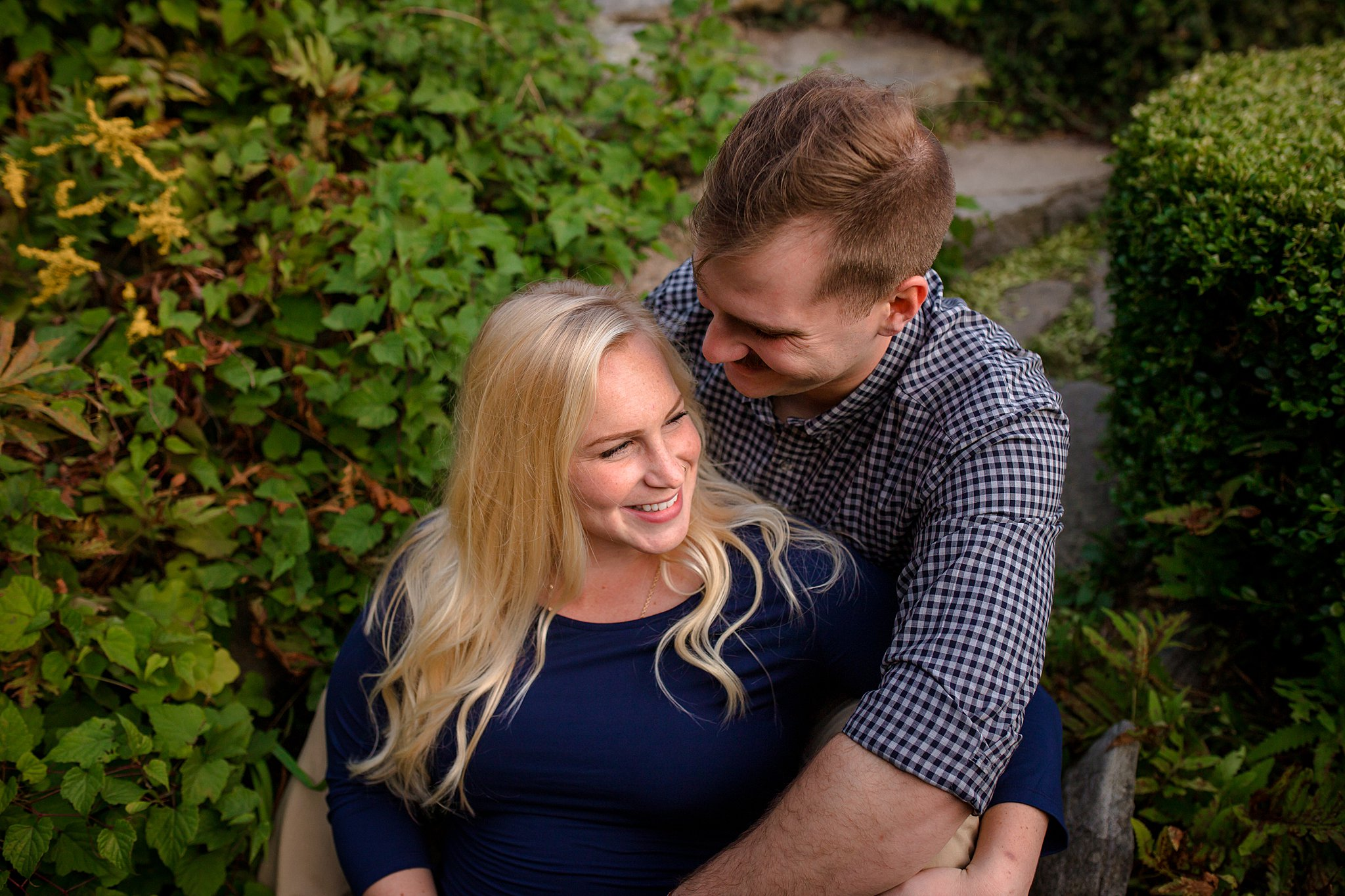 husband and wife taking maternity pictures on steps