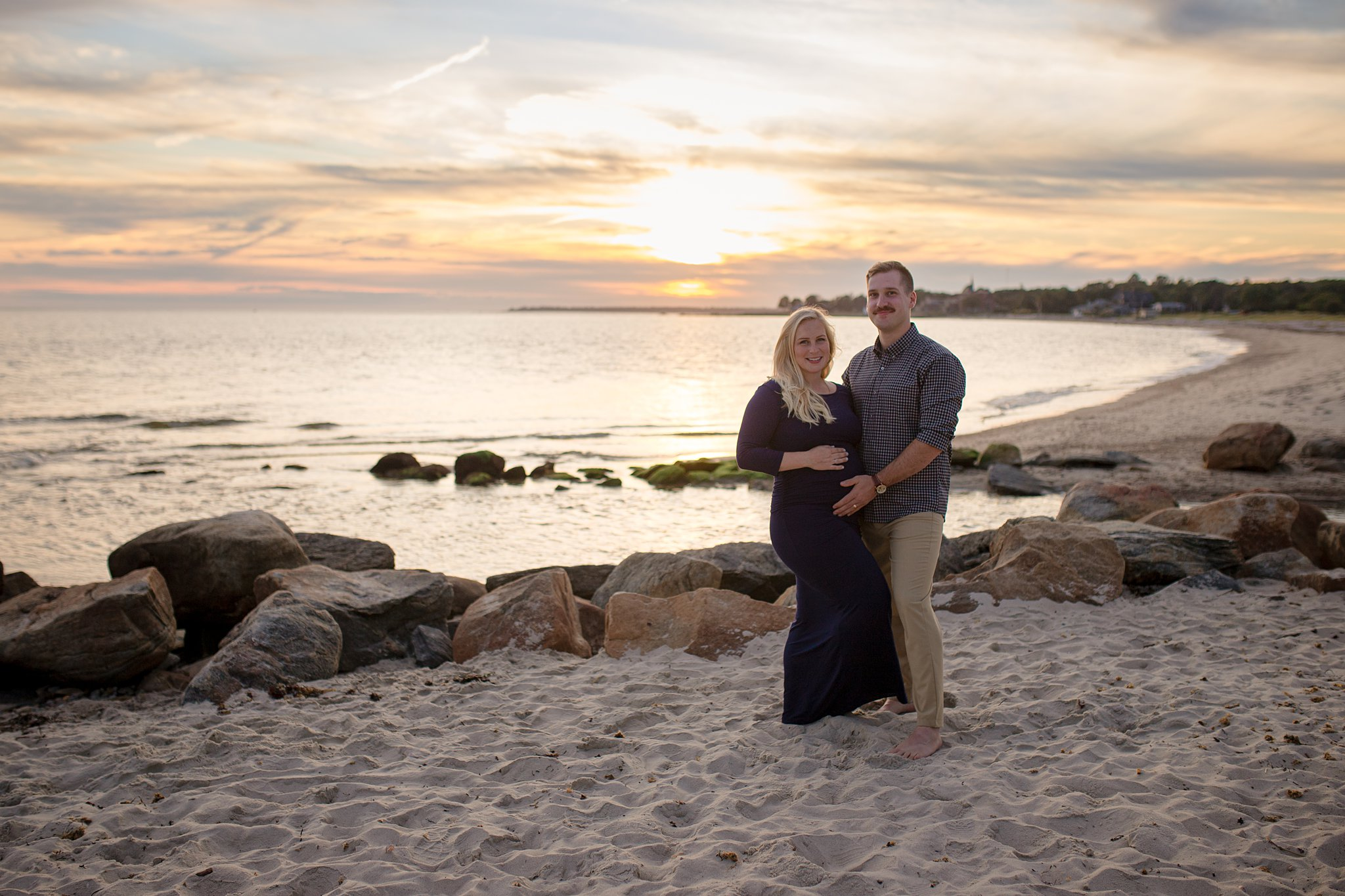 a couple at sunset on the beach for baby bump pictures