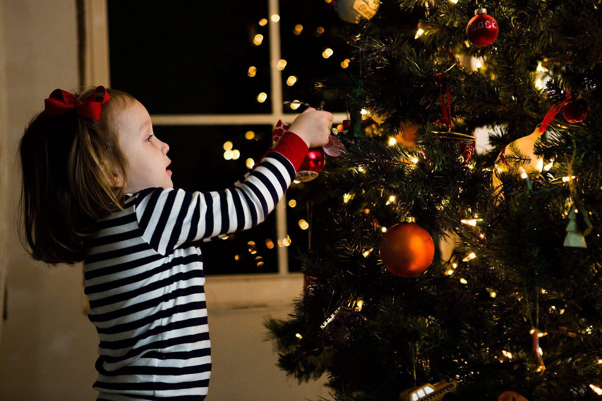 toddler decorating a christmas tree with ornaments