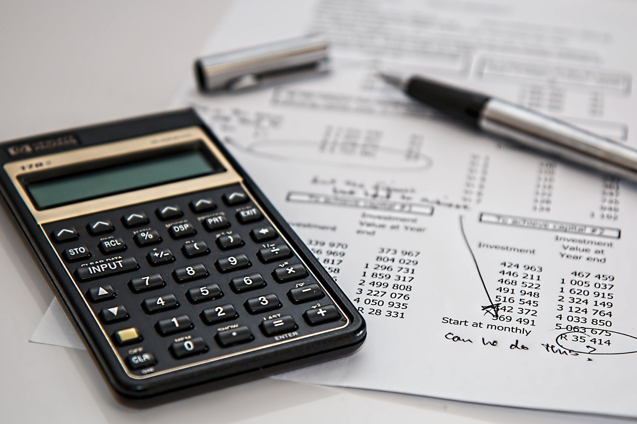 calculator and pen to paper for creating a budget