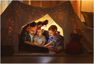 dad reading books in a tent with kids